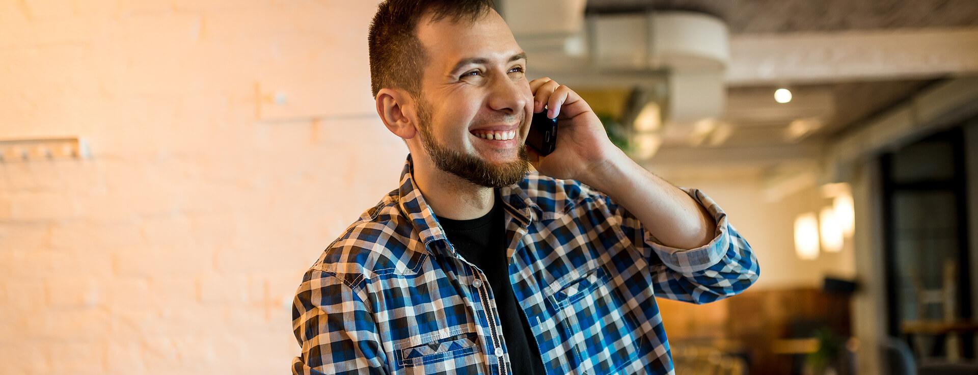 Homem sorrindo e falando no celular