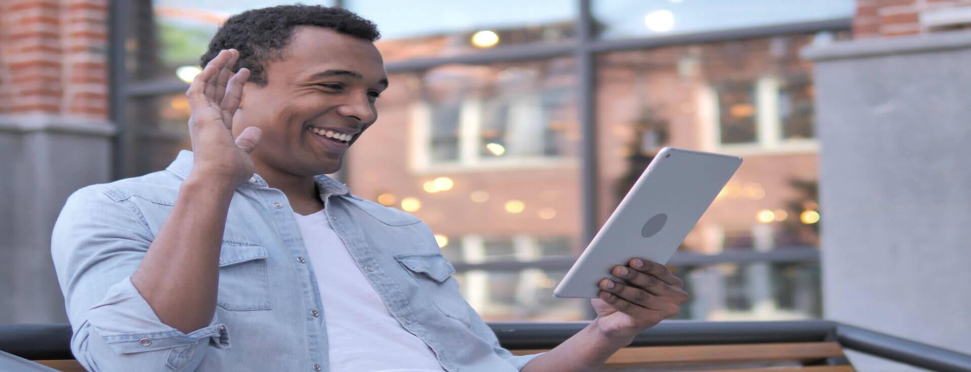 Homem sorrindo vendo tablet