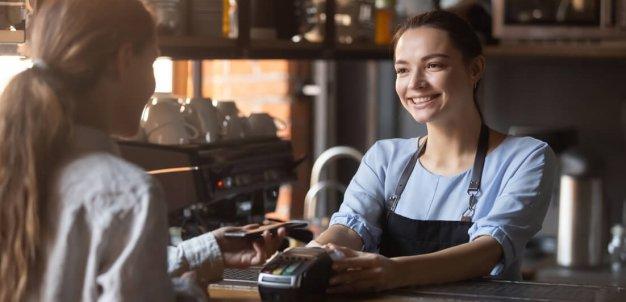 Atendente sorrindo e oferecendo máquina de cartão para cliente