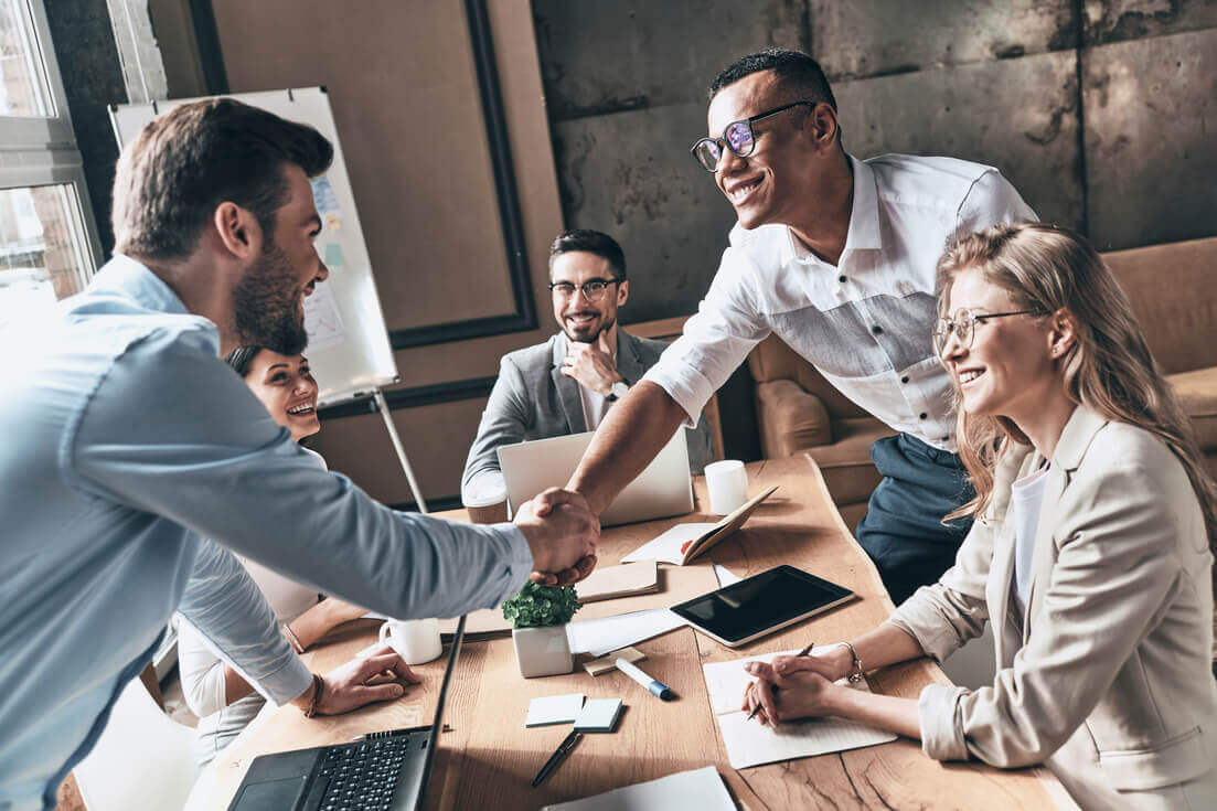 Grupo de pessoas fazendo acordo em reunião empresarial