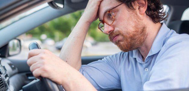 Homem ao volante com expressão descontente