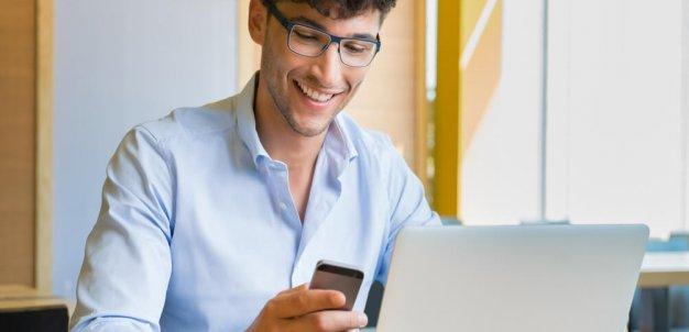 Homem manuseando ferramentas em celular e laptop