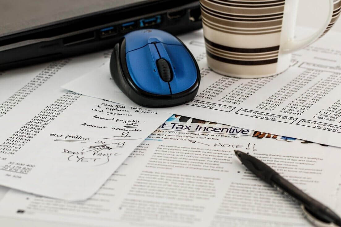 Mesa com mouse, caneca e papéis sobre escritura fiscal e tributação