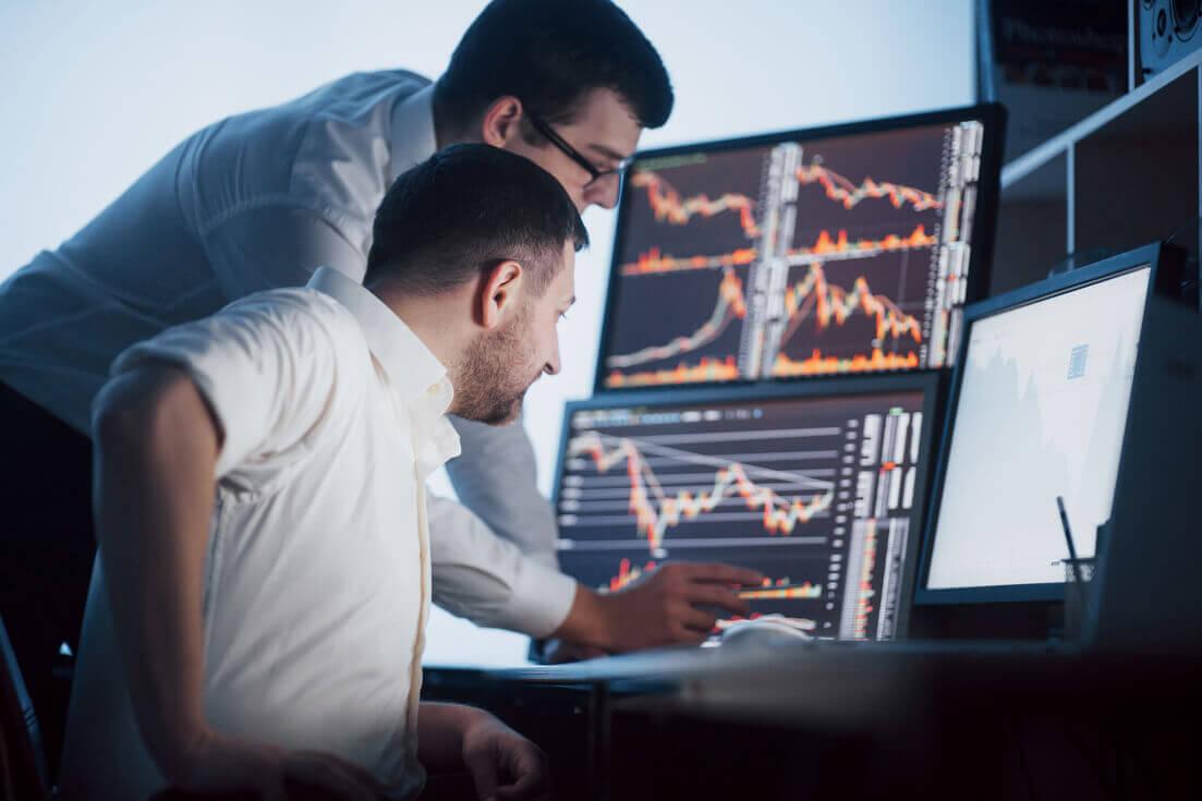 Homens em frente a computadores com gráficos