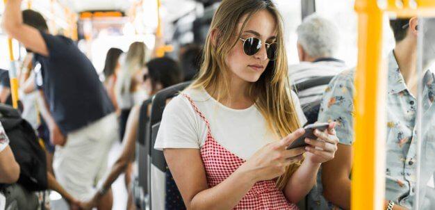 Mulher com smartphone em transporte público