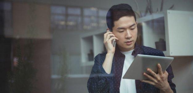 Homem olhando tablet enquanto fala ao telefone.